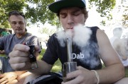 In this Aug. 16, 2013, file photo, Cody Park exhales a cloud of marijuana smoke after taking a hit on a bong at the first day of Hempfest in Seattle. A new study by the Rand Corp. suggests the market for marijuana in Washington state could be more than twice what state officials estimated last year, before voters approved Initiative 502 to set up a regulated system of recreational marijuana sales to adults. (AP Photo/Elaine Thompson, File)