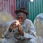 "Reggae legend Bunny Wailer smokes during a ""reasoning"" session in a yard in Kingston, Jamaica, on Aug. 28, 2014. Wailer, a founder of the iconic Wailers reggae group with late superstars Bob Marley and Peter Tosh, and fellow Rastafarians have long called for legalization of the drug that they smoke as part of their spiritual worship. (David McFadden, The Associated Press)"
