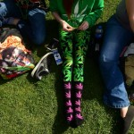 A woman rolls a joint while wearing marijuana plant inspired socks and leggings while attending the Colorado 420 Rally at Civic Center Park in Denver, Co on April 20, 2014. (Helen H. Richardson, The Denver Post)