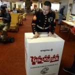 Marine Sgt. Phillip Sena, middle, and Cpl. Daniel Kravchuk, right, prepare a Toys for Tots collection box for The Courtyard at Lakewood, a retirement community. The Marines are kicking off their holiday program.  (Helen H. Richardson, The Denver Post)