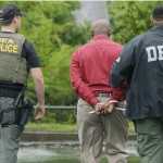 An unidentified man, center, is escorted from a medical clinic in Little Rock, Ark., by Drug Enforcement Administration officers on May 20, 2015. Early-morning raids in Arkansas, Alabama, Louisiana and Mississippi were the final stage of an operation launched last summer by the DEA's drug diversion unit, a senior DEA official said. (Danny Johnston, AP)