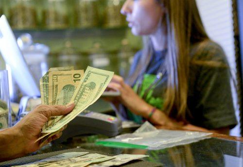 A medical marijuana customer counts out cash for a transaction at Native Roots in unincorporated Boulder County in this 2016 file photo.